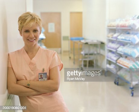 Female nurse leaning against wall, arms crossed, portrait : Stock Photo