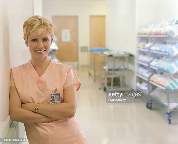 Infirmière s'appuyant sur le mur, les bras croisés, portrait