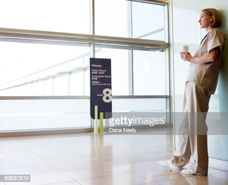 Female nurse looking out window in hospital    : Stock Photo