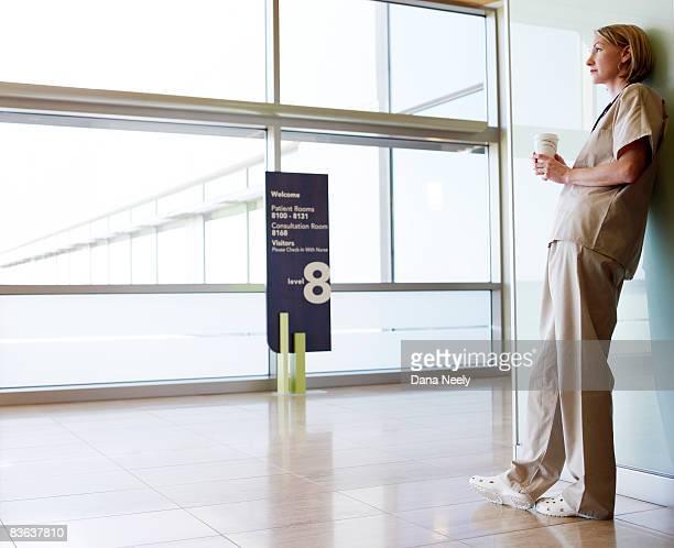 Female nurse looking out window in hospital