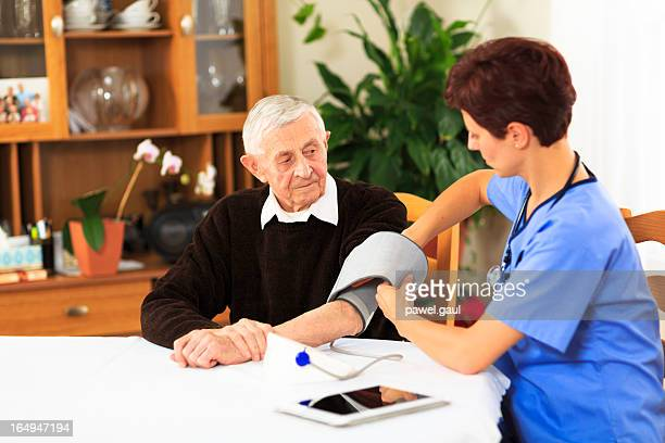 Female nurse measuring blood pressure of elderly patient