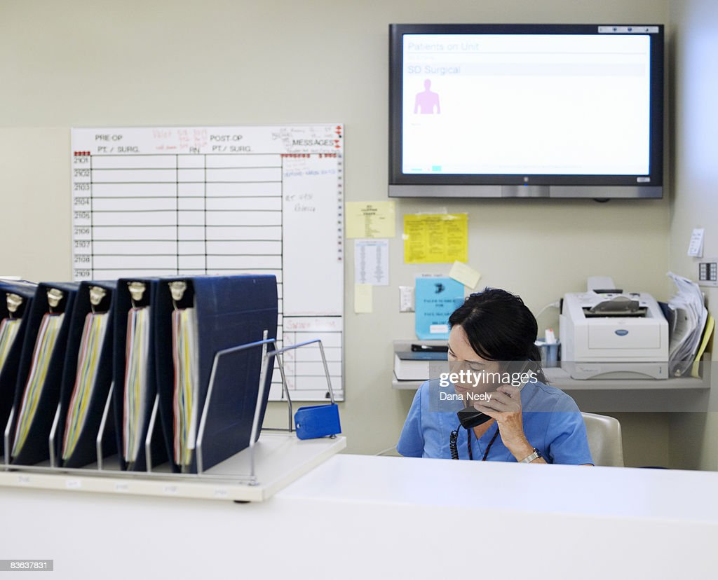 Female nurse on phone in outpatient/recovery       : Stock Photo