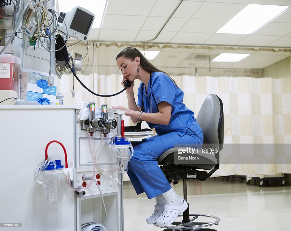 Female nurse on phone in PACU of hospital  : Stock Photo