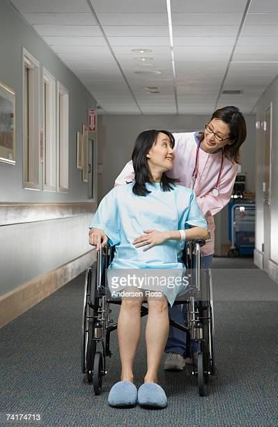 'Female nurse pushing pregnant woman in wheelchair, smiling'