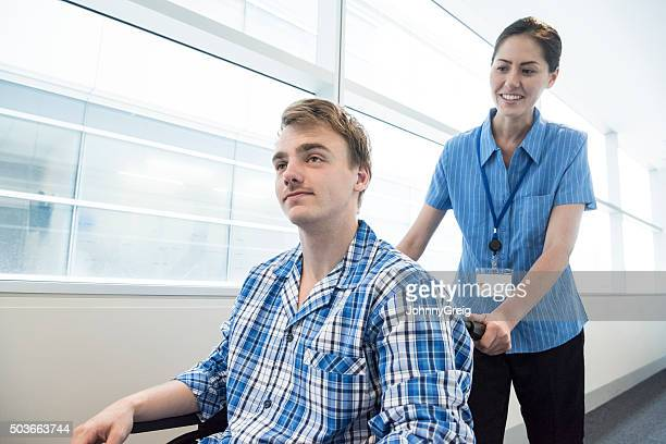 Female nurse pushing young man in wheelchair