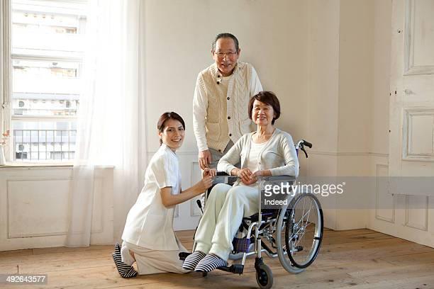 Female nurse, senior woman in wheelchair, and senior man smiling