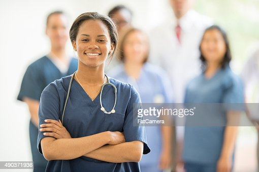 Female Nurse Standing and Smiling with Associates