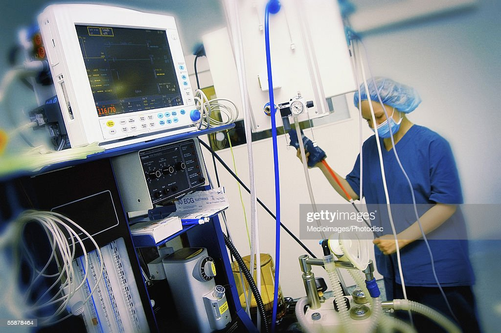 Female nurse standing in an operating room : Stock Photo