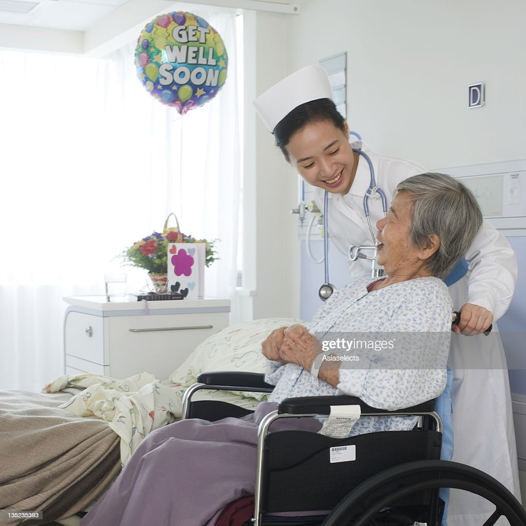 Female Nurse Taking Care Of A Patient And Smiling Stock ...