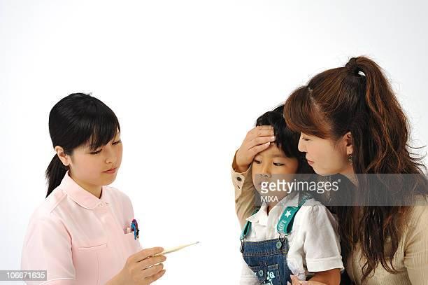 Female nurse taking girl's temperature