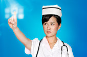Female nurse using futuristic touch screen over blue background