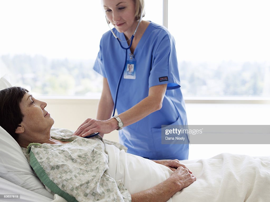 Female nurse using stethoscope on senior woman     : Stock Photo