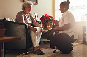 Senior woman sitting on a chair at home with female caregiver holding blood pressure gauge.  Female nurse visiting senior patient for checking blood pressure.