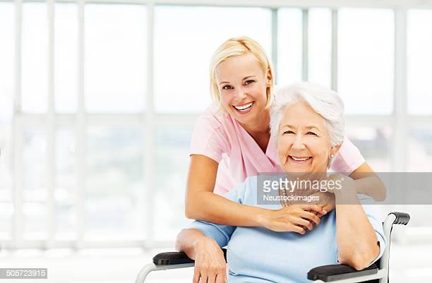 Female Nurse With Arms Around Senior Patient On Wheelchair