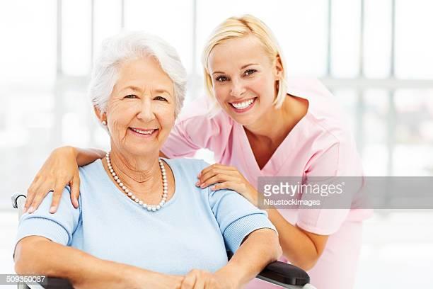 Mujer enfermera con paciente Senior para silla de ruedas
