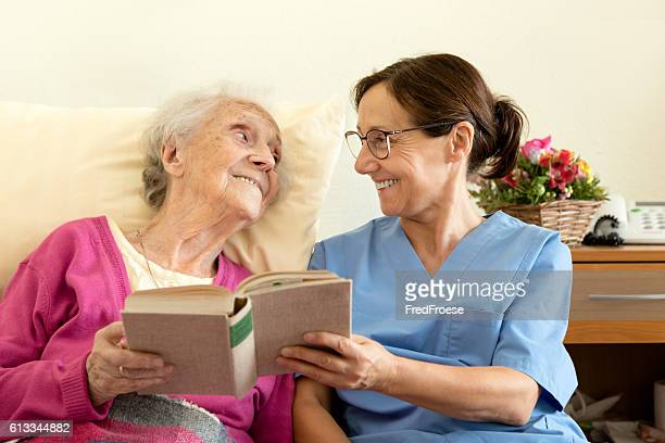 Female nurse with senior woman patient, reading a book
