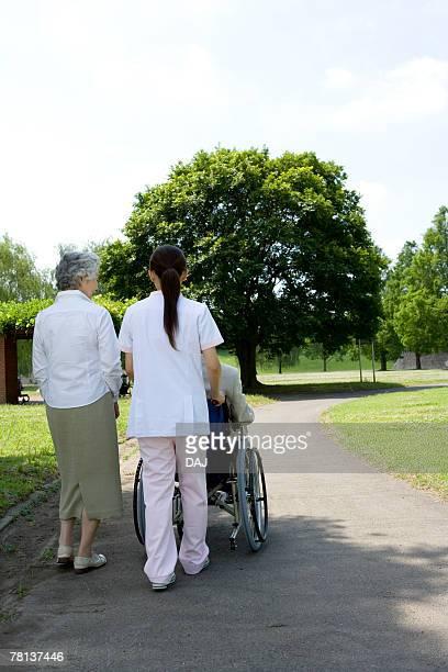 Female nurse with senior woman pushing senior man in wheelchair