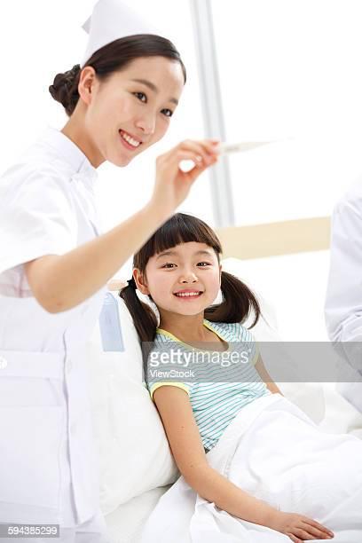 Female nurses in the small girl to measure body temperature