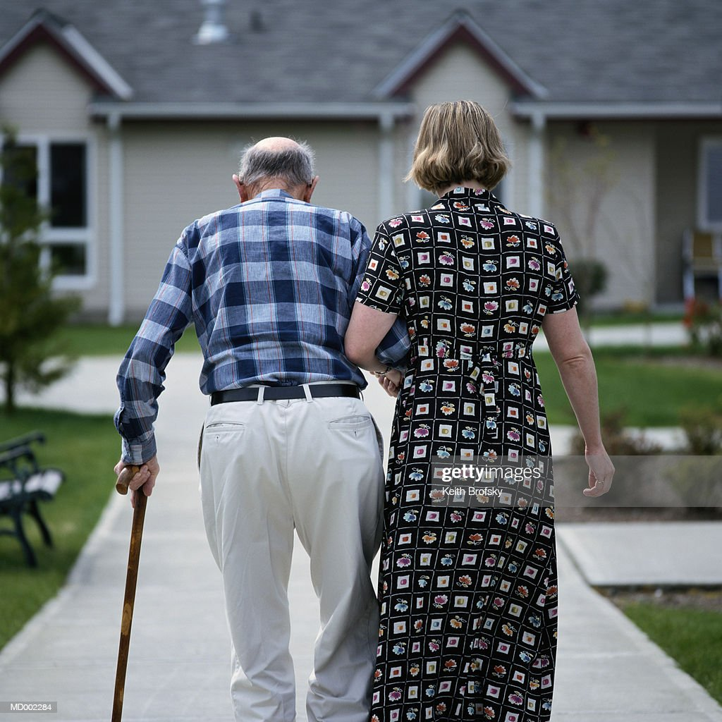 Female nursing assistant helping senior man walk, rear view : Stock Photo