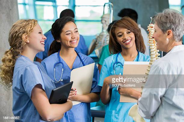 Female nursing or medical students studying spine model in class