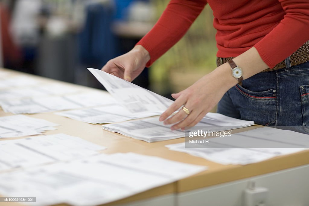 Female office worker arranging document on desk, mid section : Stock Photo