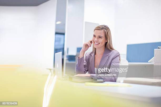 Female office worker at desk, smiling