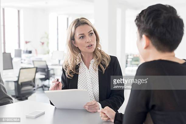 Female office worker discussing with colleague in modern office