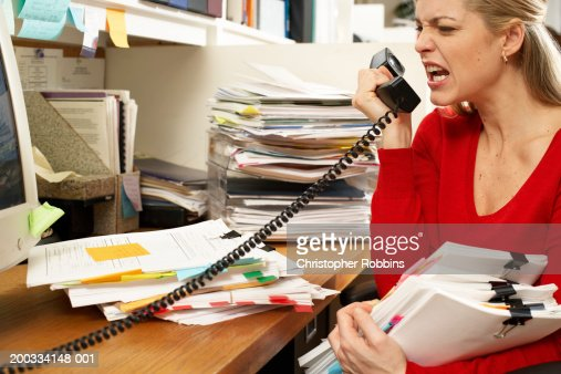 Female office worker holding paperwork, snarling at phone handset : Stock Photo