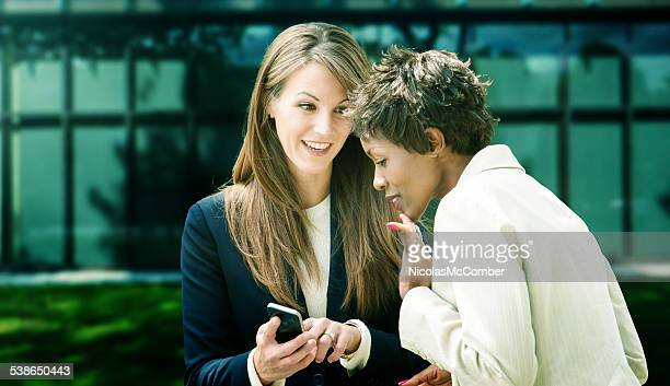 Female office worker shares information on mobile phone to colleague