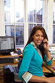Female office worker sitting at desk, using phone, smiling, portrait