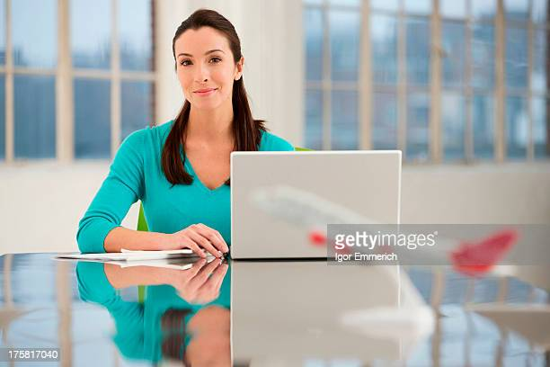 Female office worker sitting at desk with laptop