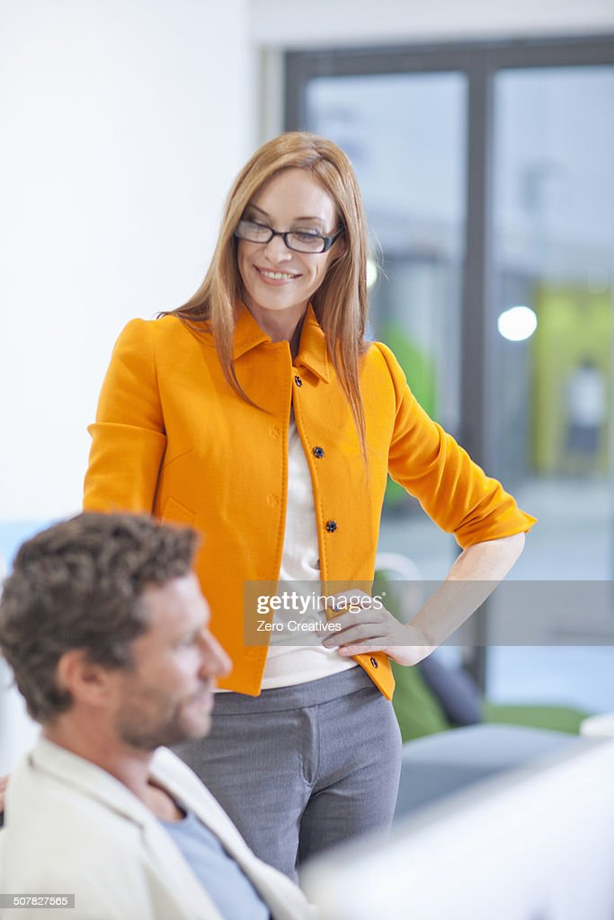 Female office worker smiling, hand on hip