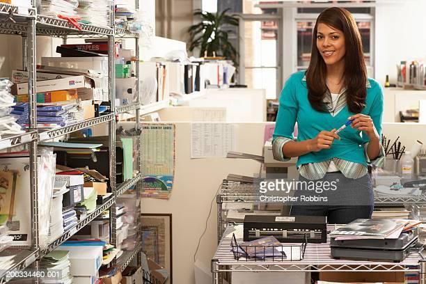 Female office worker standing in storage area, holding pen, portrait