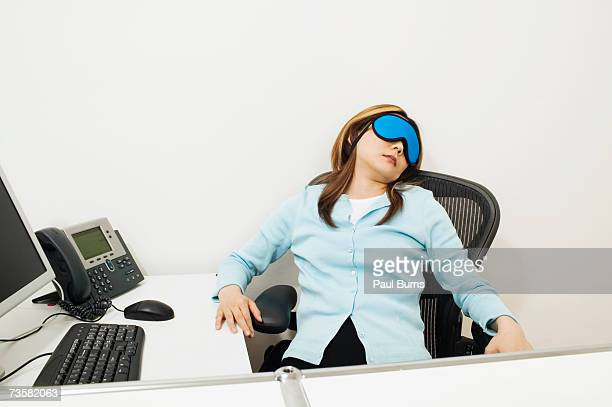 Female office worker taking a nap at desk in cubicle in office