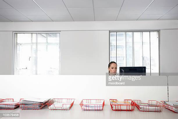 Female office worker using computer in office cubicle behind trays with documents