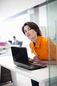 Female office worker using laptop, leaning forward