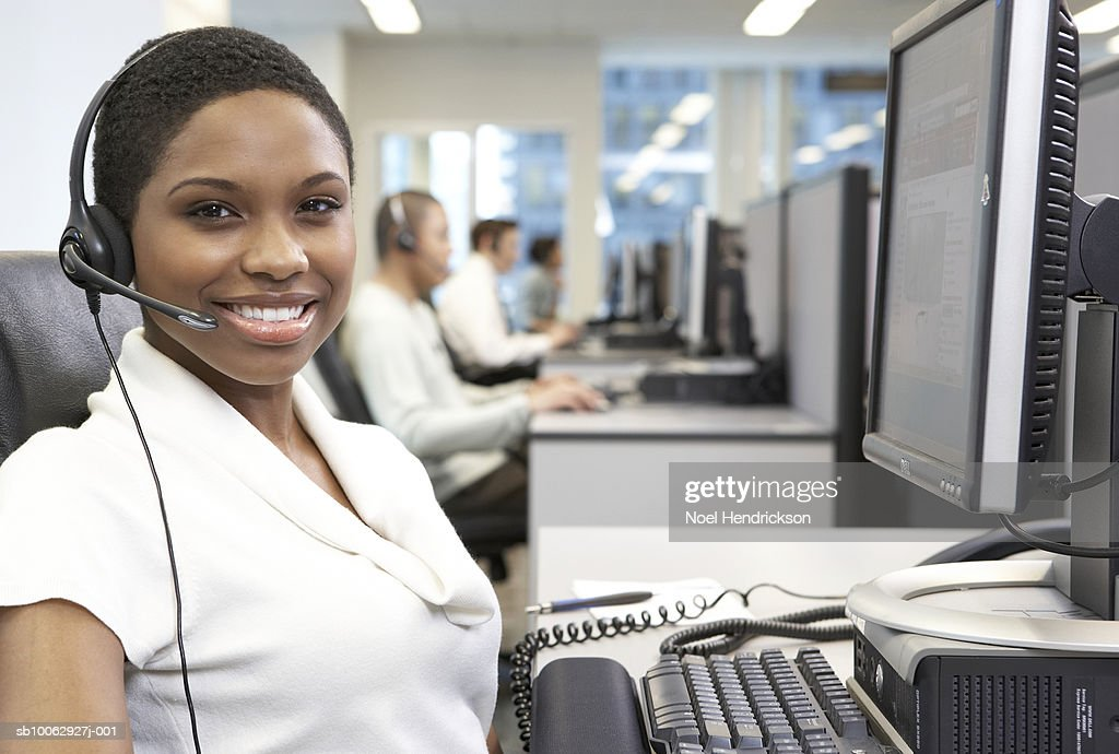 Female office worker wearing headset at computer workstation, portrait : Stock Photo