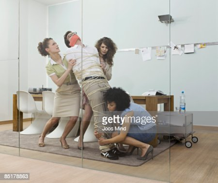 female office workers trying to carry tied up man