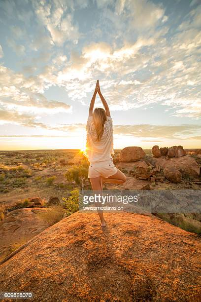 Female on boulder exercises yoga at sunrise
