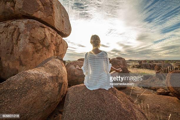 Female on boulder exercises yoga at sunset