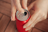 Female opening a can of tin