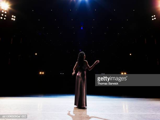 Female opera singer performing solo on stage, rear view