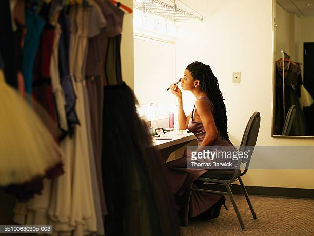Female opera singer putting on make-up in dressing room