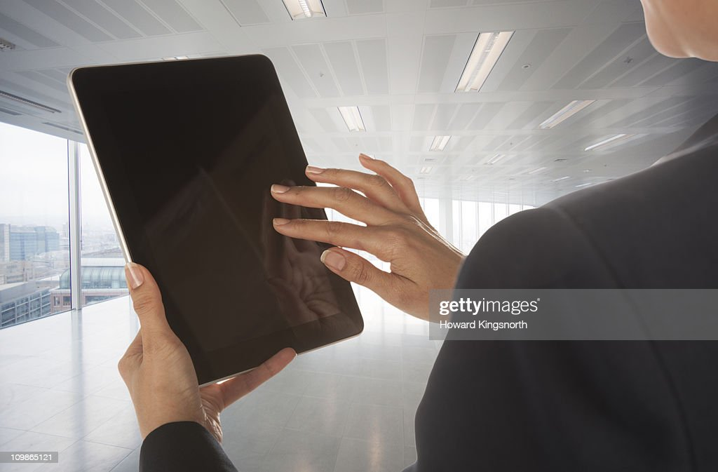 female operating digital tablet tablet in empty office : Stock Photo