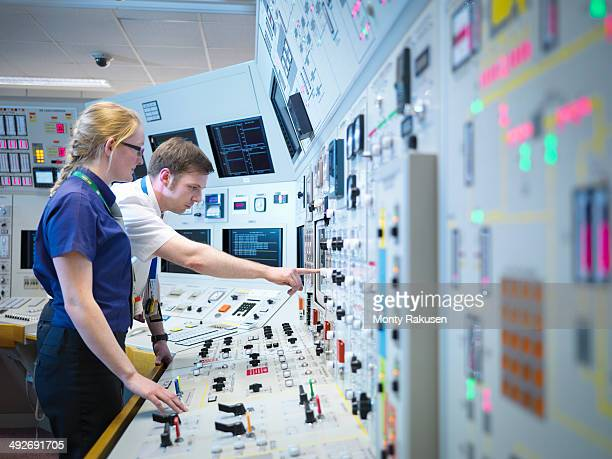 Female operator and trainee in nuclear power station control room simulator