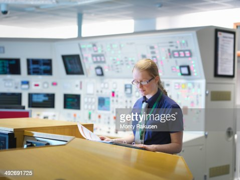 Female operator reading notes in nuclear power station control room simulator