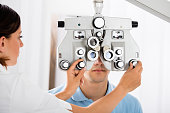 Female Optometrist Adjusting Phoropter For Male Patient In Clinic