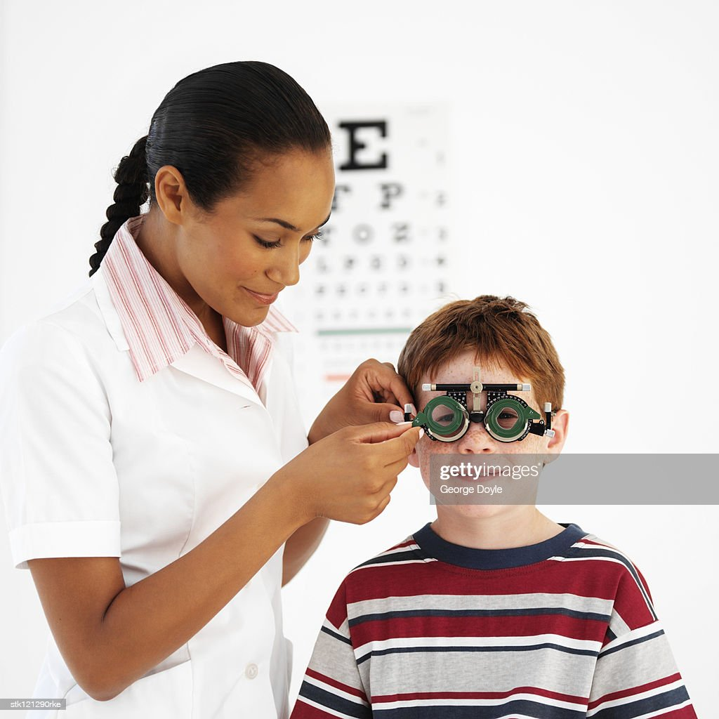Female optometrist examining a boy's (8-10) eyes : Stock Photo