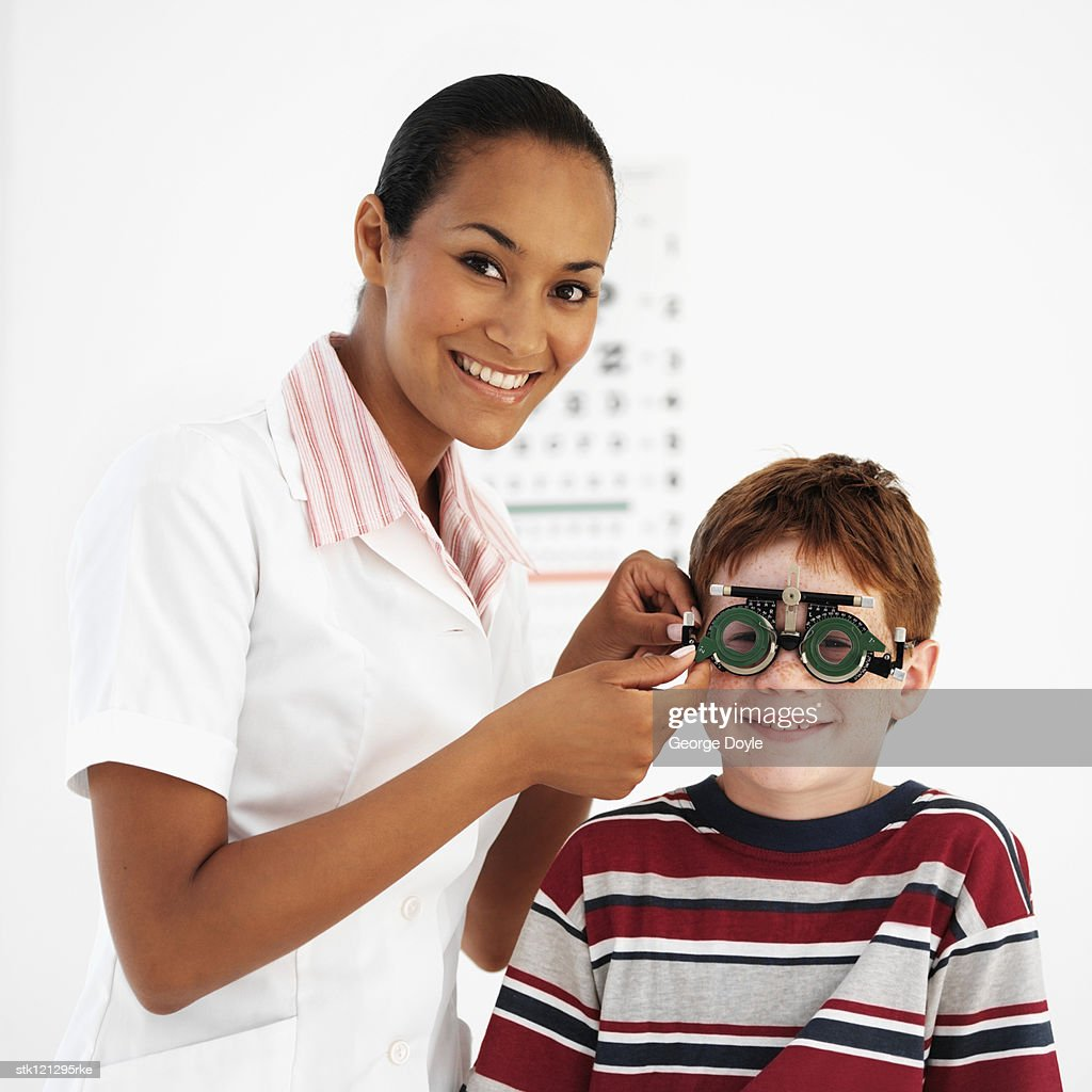 Female optometrist examining a boy's (8-10) eyes : Stock Photo