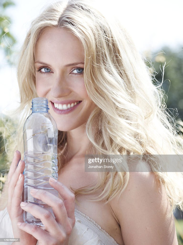 Female outside holding bottle of water : Stock Photo